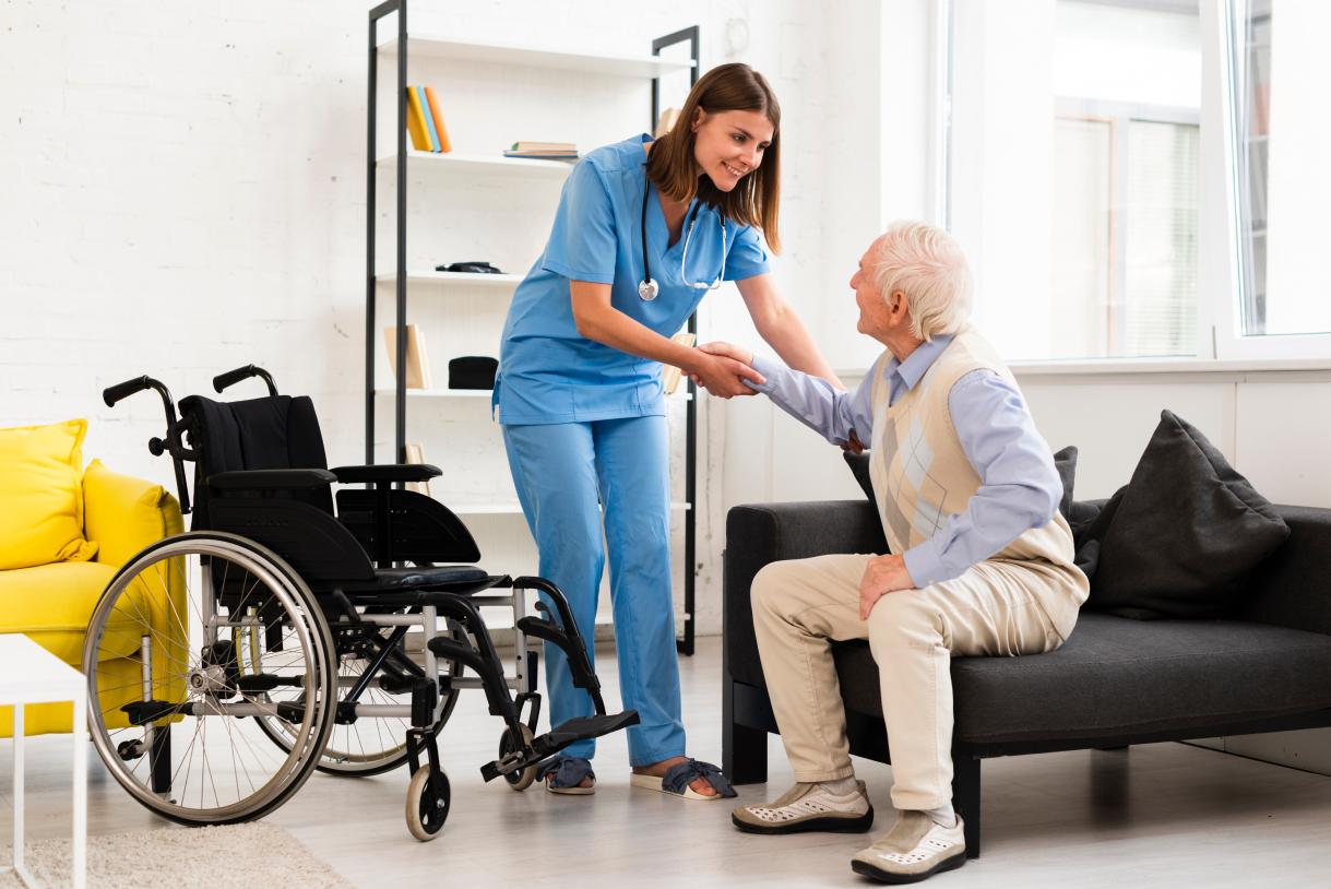 long-shot-nurse-helping-old-man-getting-up 1